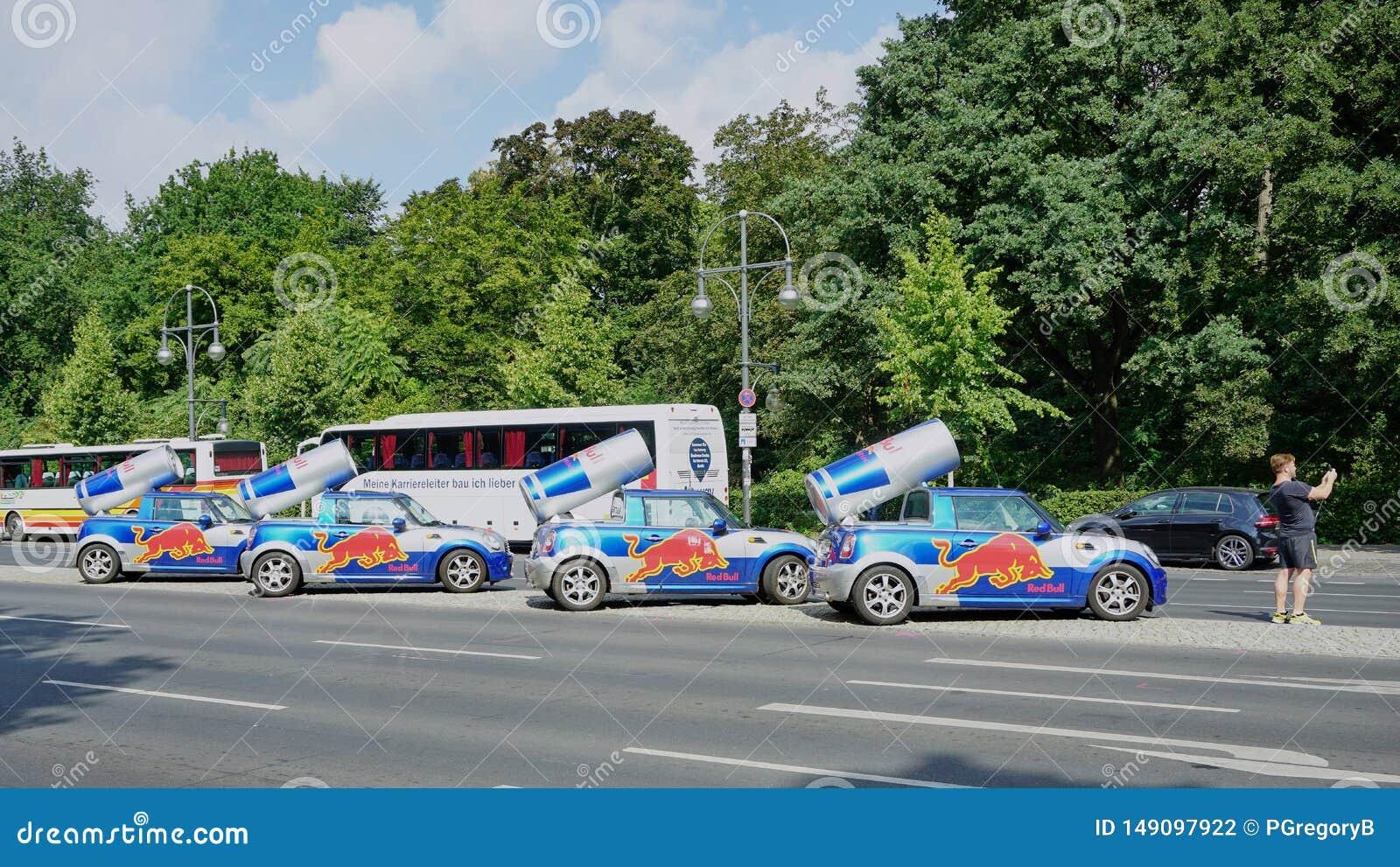 El hombre toma el selfie con cuatro latas de Red Bull encima de BMW Mini Cars