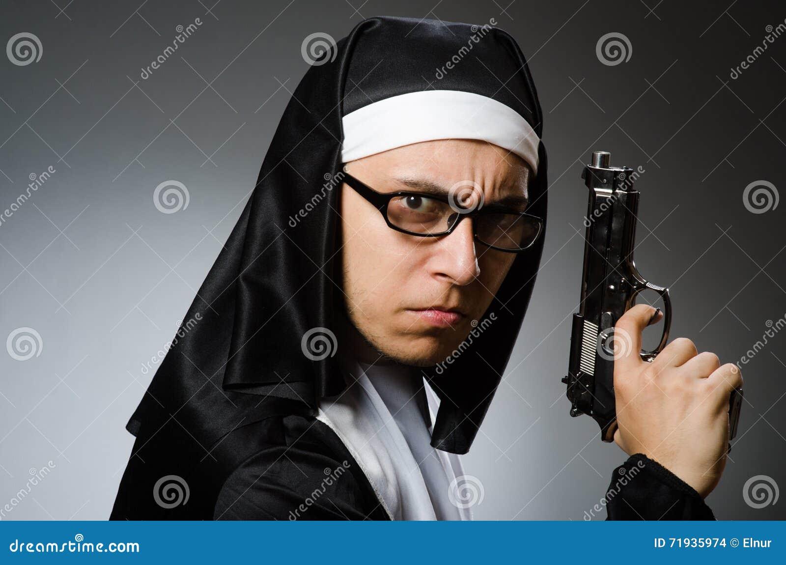 El Hombre Vestido Como Monja Con La Arma De Mano Foto De