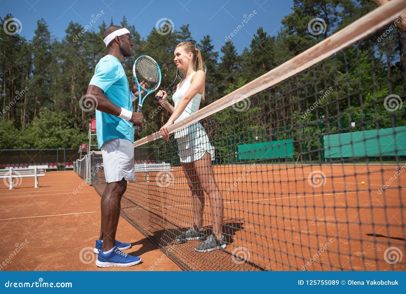 El hombre y la mujer alegres están jugando a tenis cara a cara