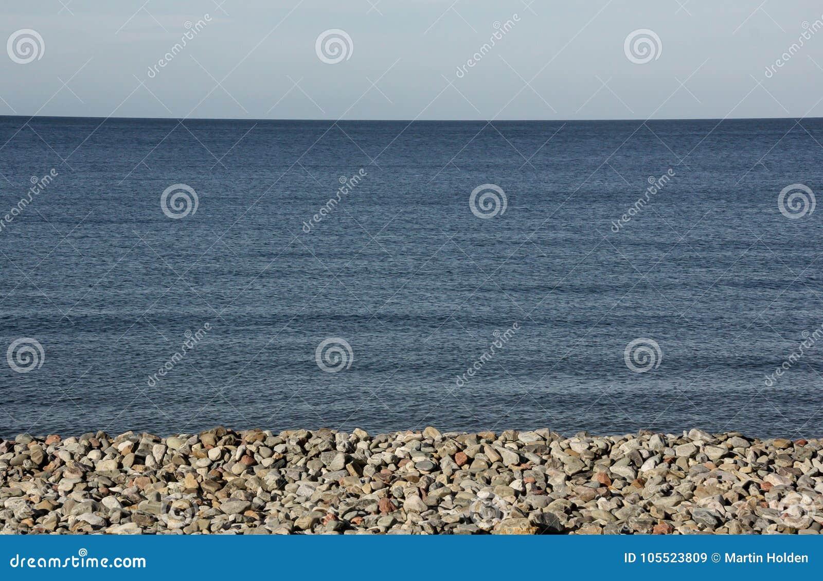 El horizonte azul como la playa pebbled y considera la reunión el cielo