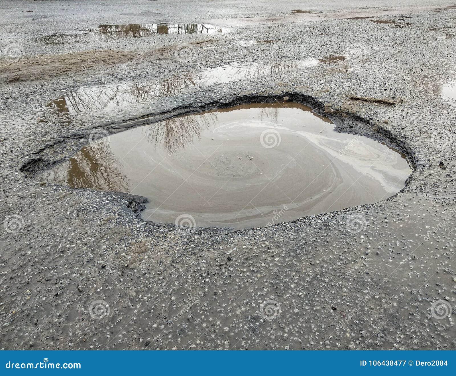El hoyo grande llenó de agua en la cubierta del asfalto, camino roto, reflexión del ambiente en el agua, caminos ucranianos