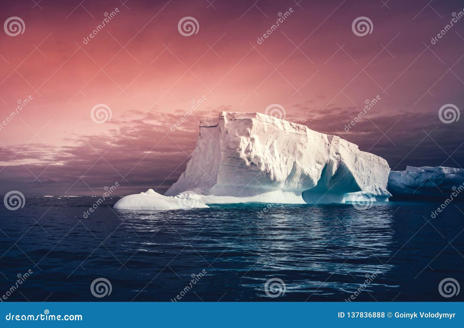 El iceberg enorme en el fondo colorido del cielo