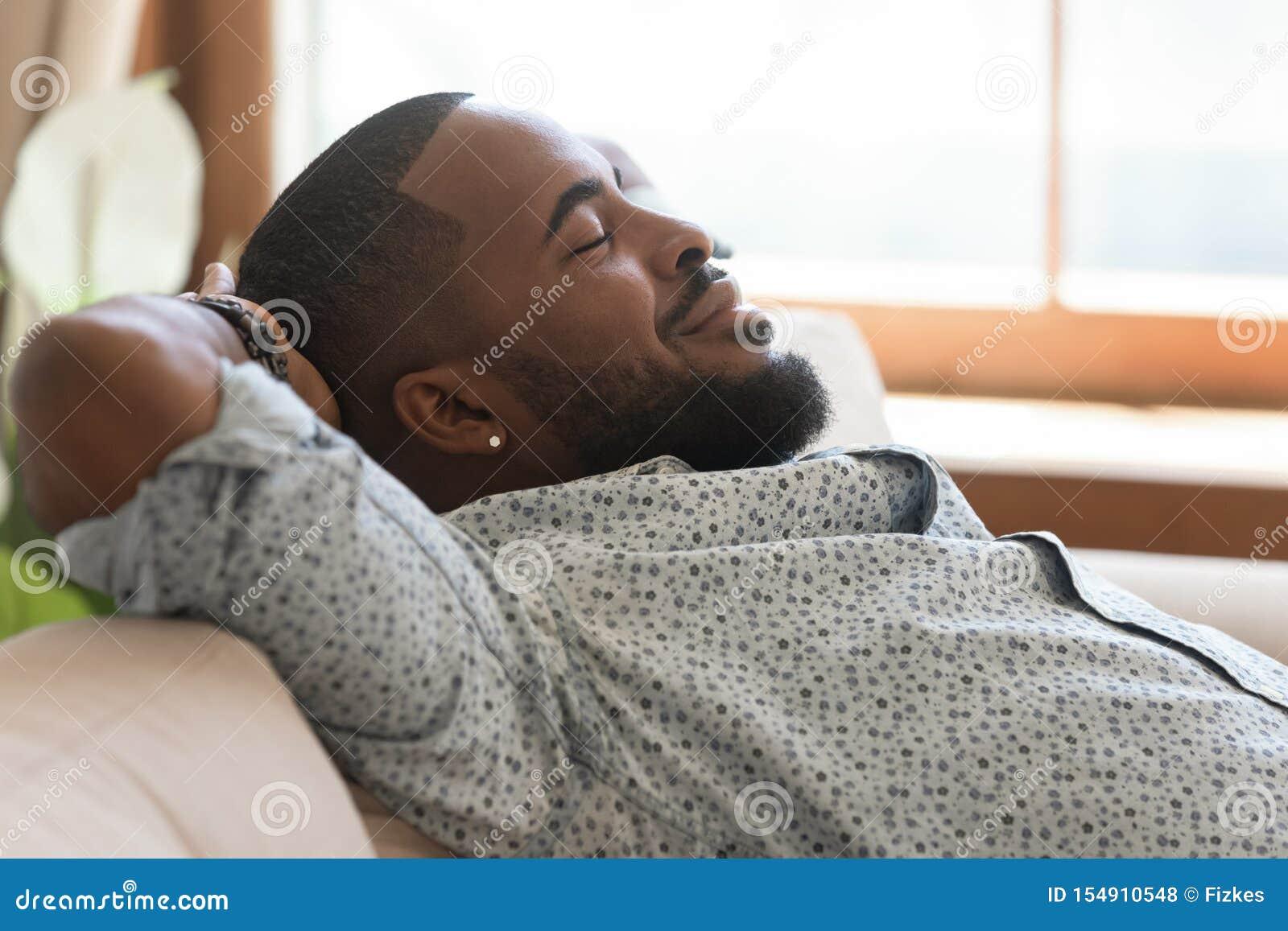 El inclinarse de relajación afroamericano perezoso tranquilo del hombre joven en el sofá