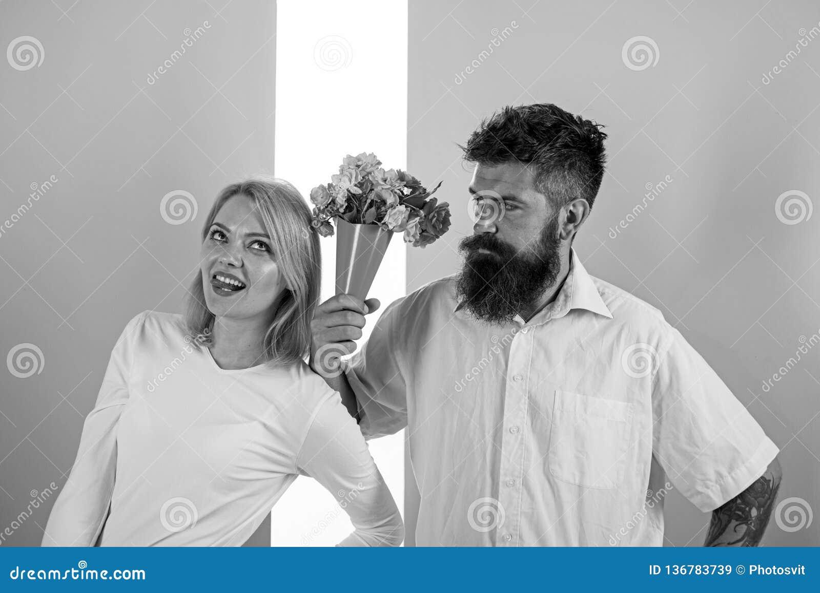 El inconformista barbudo da gesto de la excusa de la muchacha de flores del ramo Hombre con la mujer de los apologyes de la barba