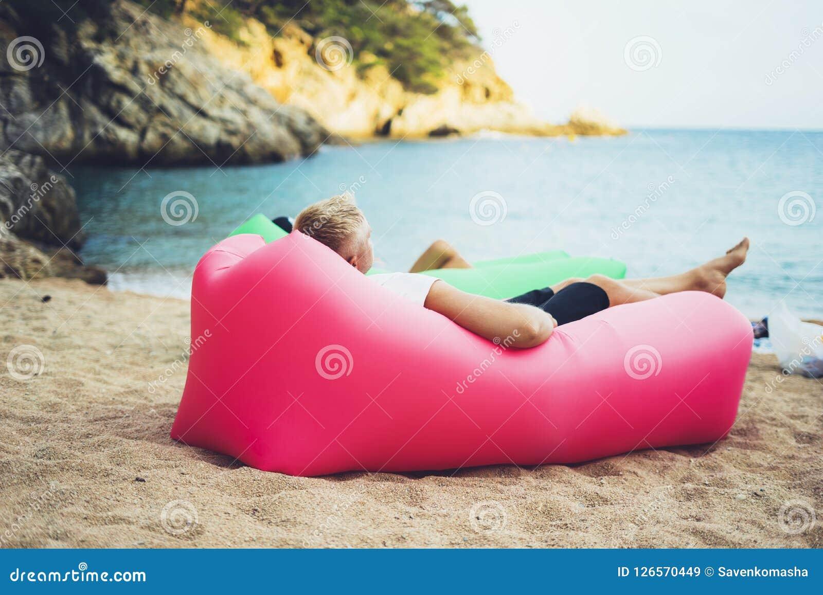 El inconformista joven que se relaja en la playa de la costa costa en el sofá perezoso inflable del taburete del aire, turista de