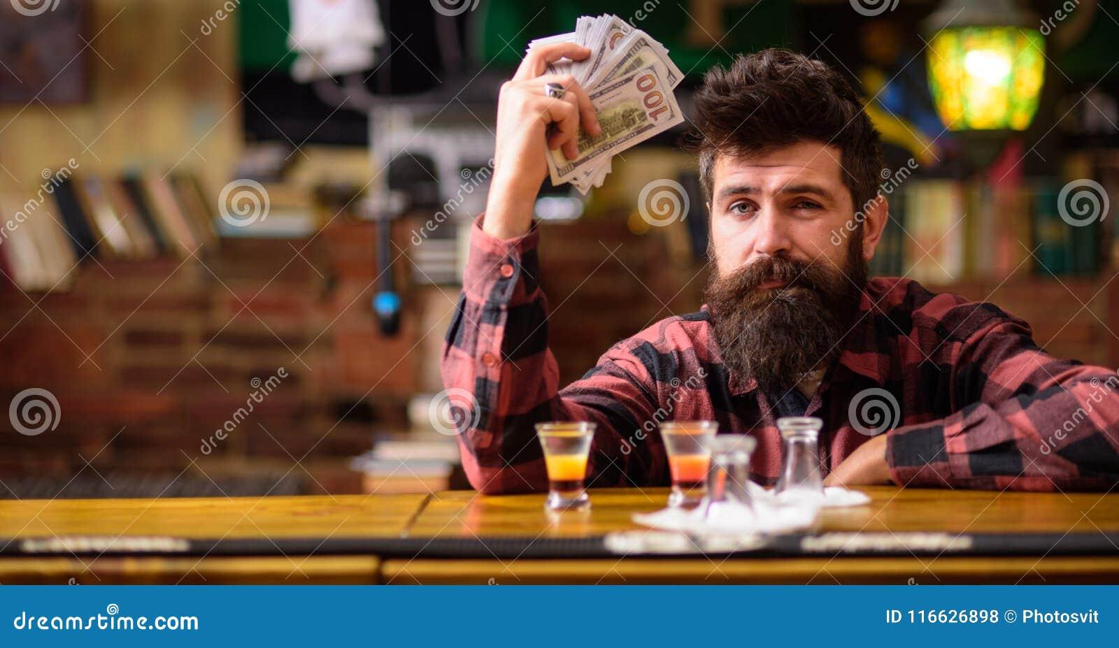 El inconformista sostiene el dinero, contando efectivo para comprar más alcohol