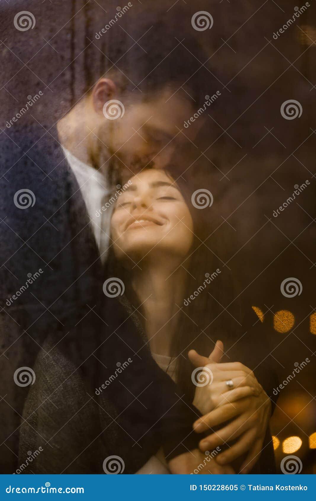 El individuo de amor abraza y besa su situación feliz de la novia detrás de una ventana mojada con las luces Pares rom?nticos