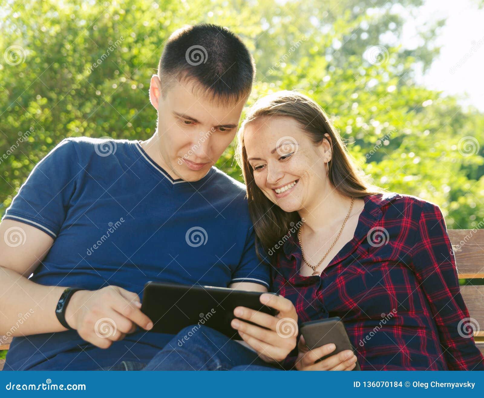 El individuo en una camiseta azul y la muchacha en camisa de tela escocesa están mirando sus fotos del viaje