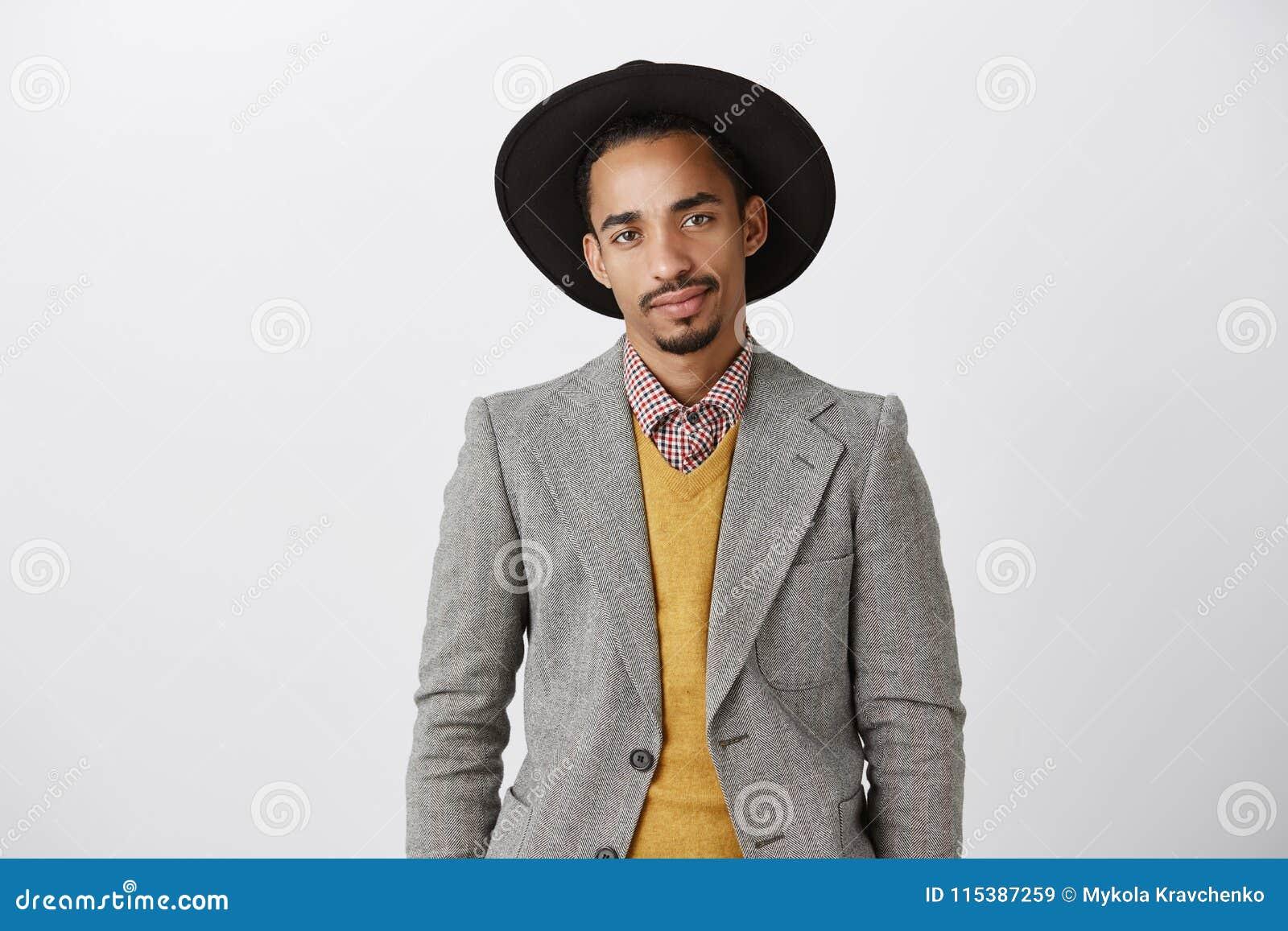 El individuo es levemente intenso durante entrevista Retrato del afroamericano hermoso serio en chaqueta de moda y sombrero negro