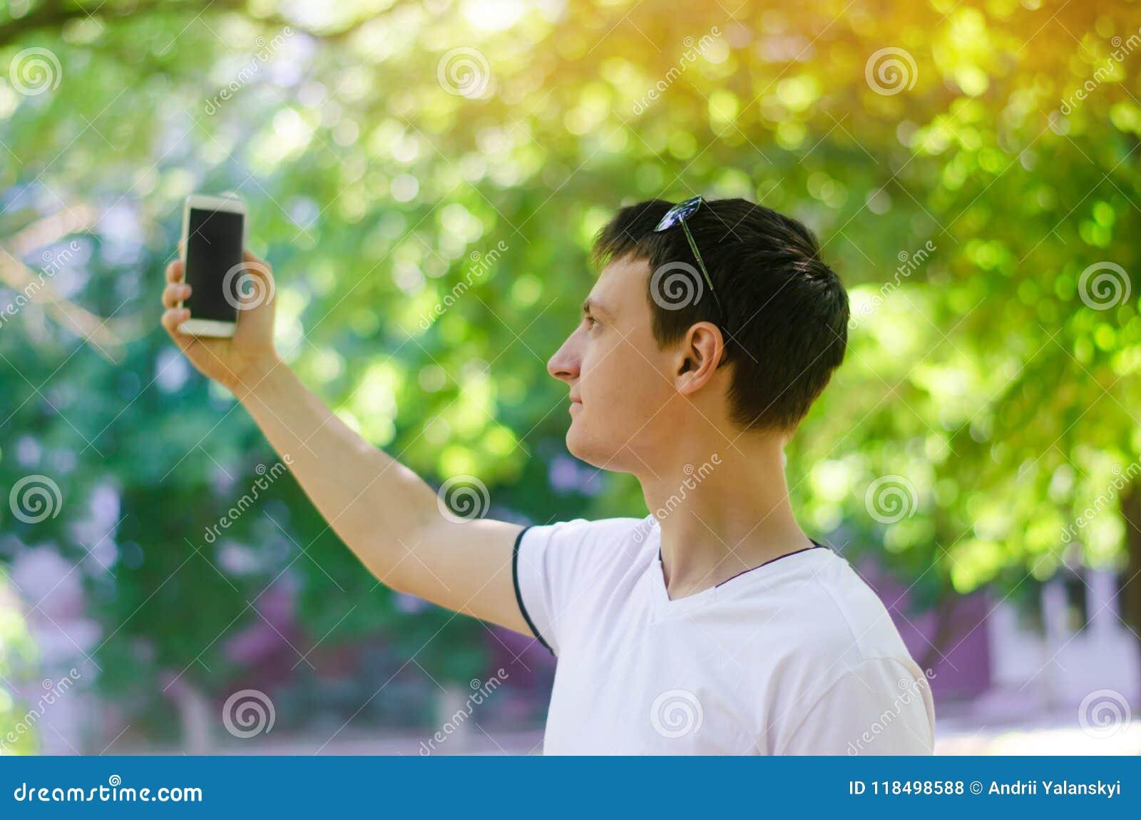 El individuo europeo joven hermoso que toma imágenes de sí mismo y hace que el selfie en una ciudad parquea al aire libre forma d