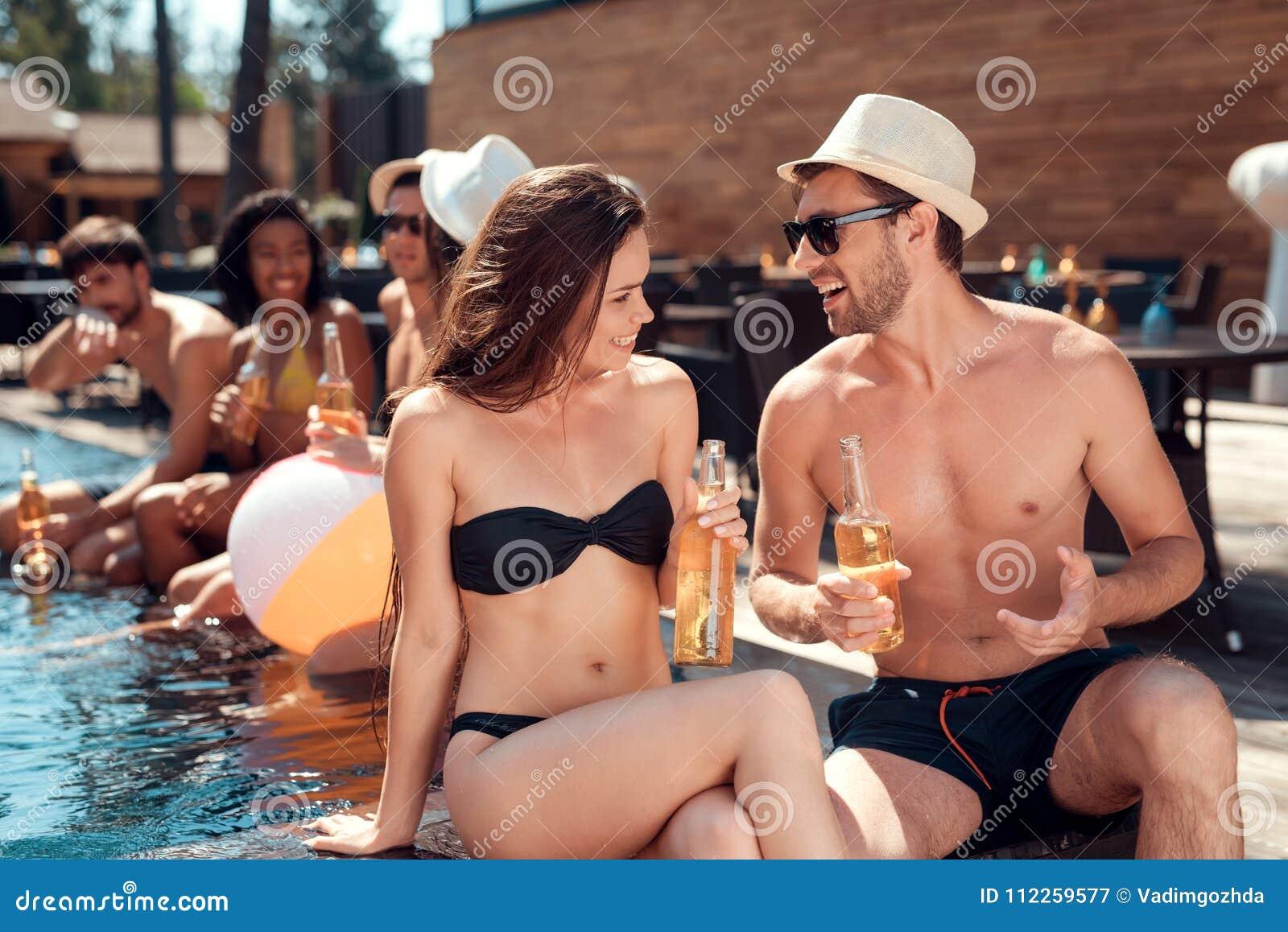 El individuo joven en sombrero de paja del verano liga con la muchacha en el traje de baño que se sienta en piscina Fiesta en la