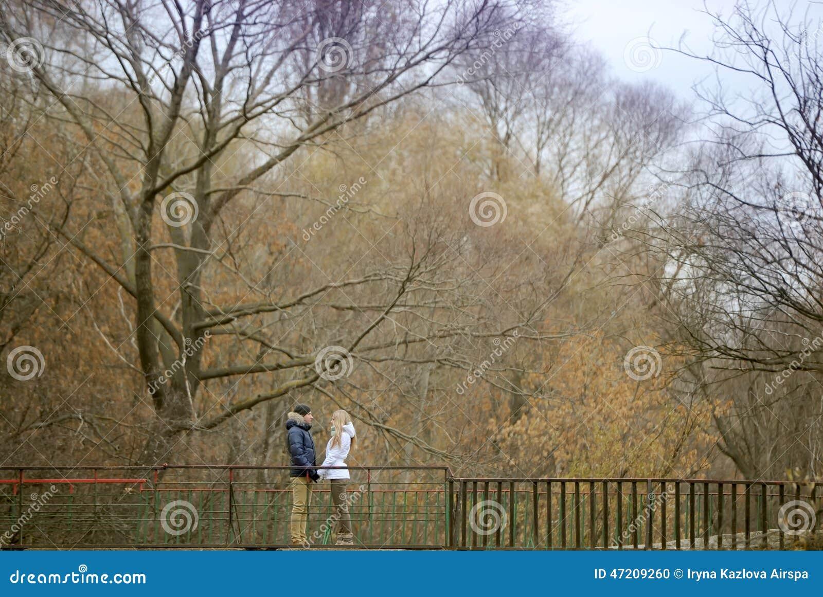El individuo y la muchacha caminan en el parque del otoño