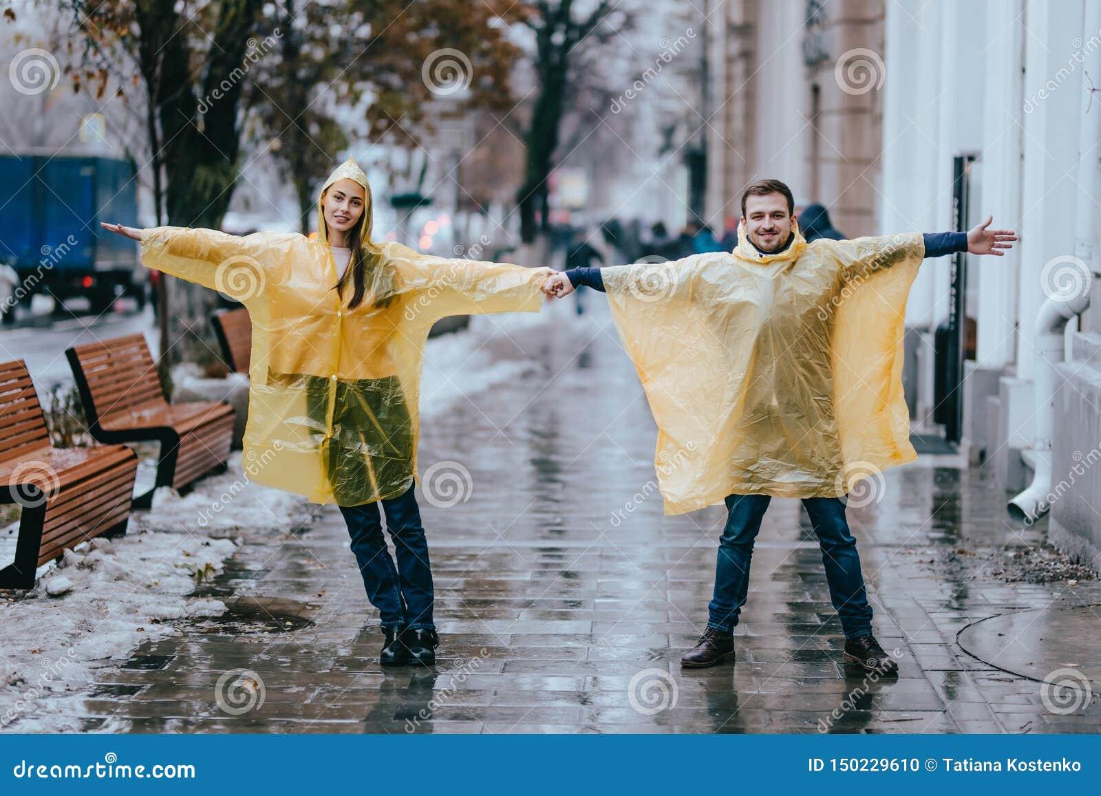 El individuo y la muchacha de amor vestidos en impermeables amarillos se colocan en la calle bajo la lluvia