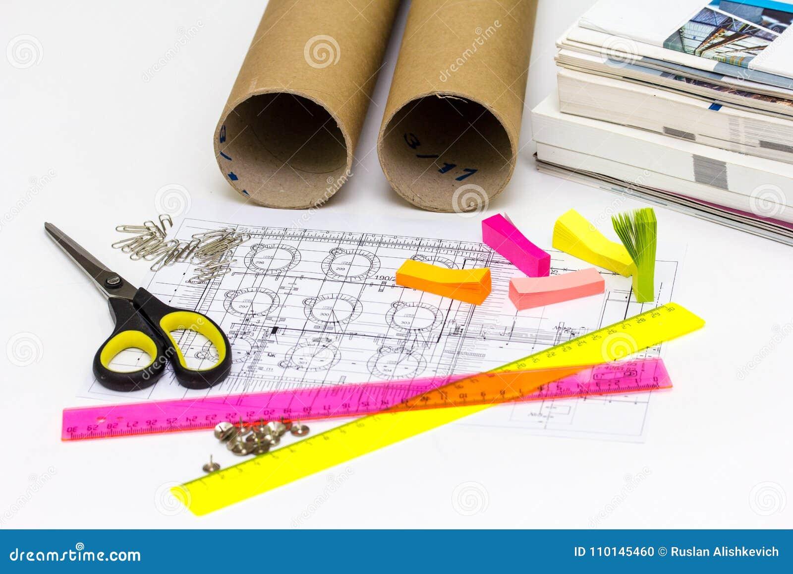 El ingeniero del lugar de trabajo tiene los modelos, tijeras, reglas, etiqueta engomada