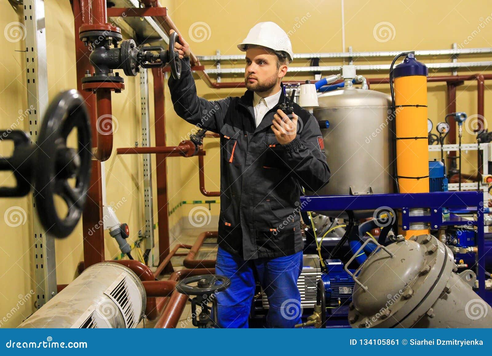 El ingeniero del técnico abre la válvula de puerta de la tubería en refinería de petróleo