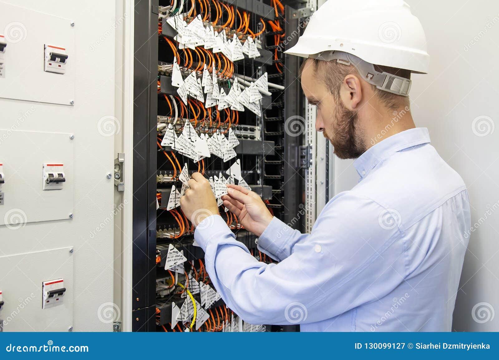 El ingeniero del técnico conecta fibras ópticas en el interruptor de la comunicación en centro de datos Hombre del servicio en da