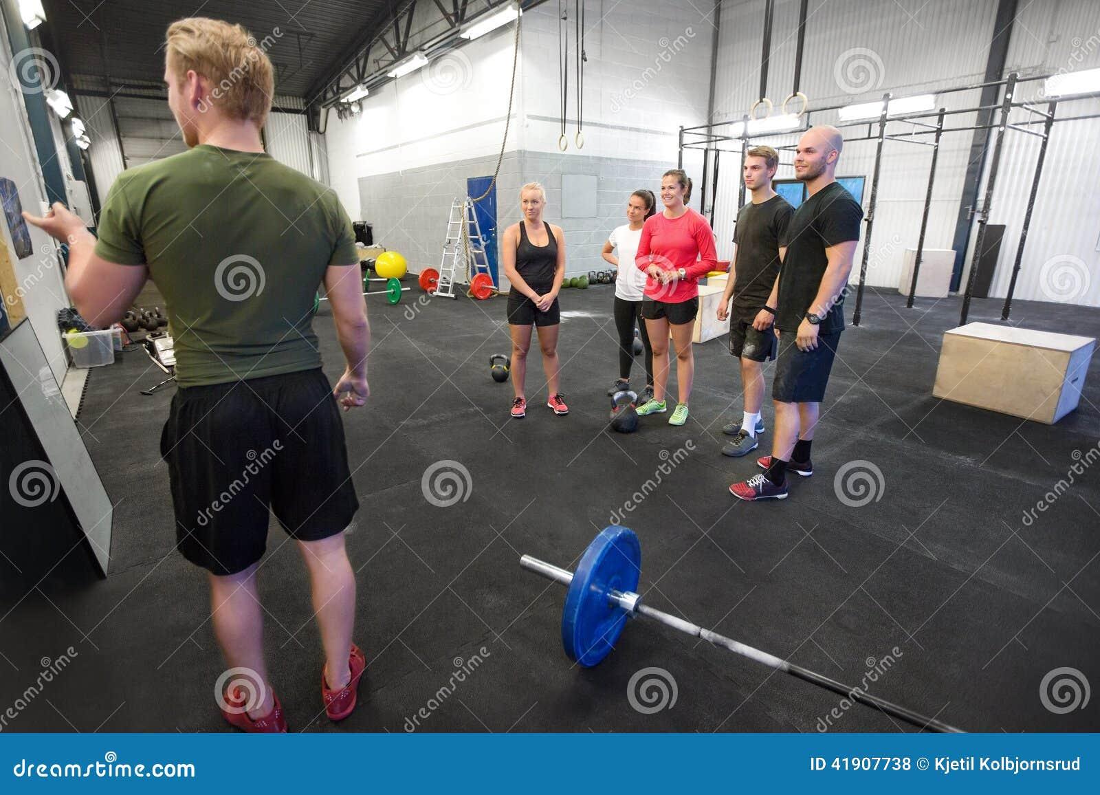 El instructor enseña a su equipo de la aptitud en el gimnasio