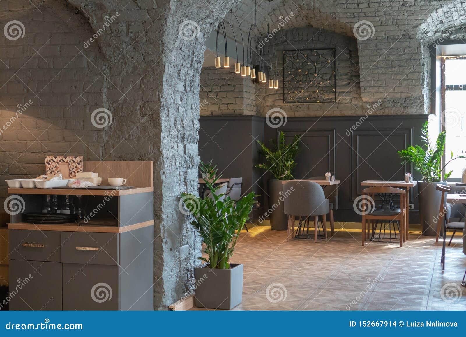El interior de un restaurante acogedor en el estilo del desván Café elegante con una pared gris del ladrillo