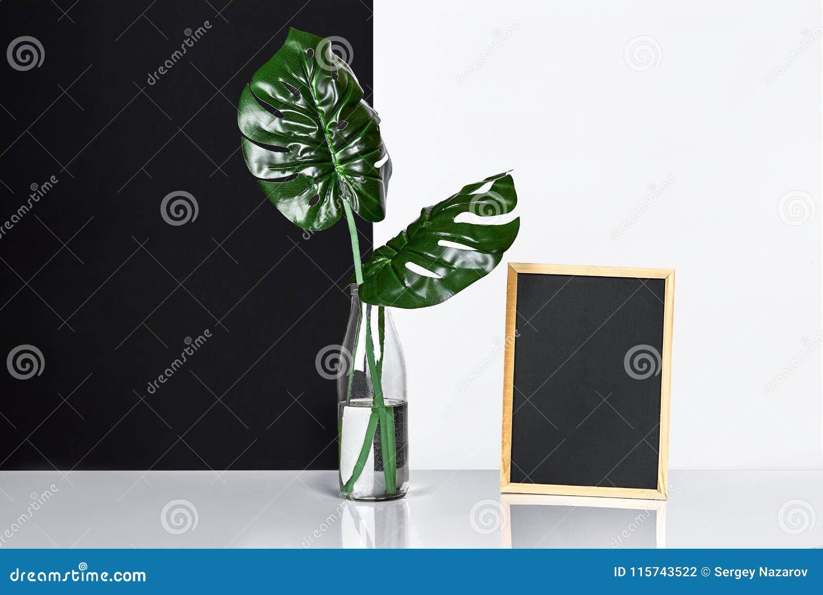 El interior elegante con mofa encima del marco del cartel, hojas en la botella de cristal en la tabla con la pared blanco y negro