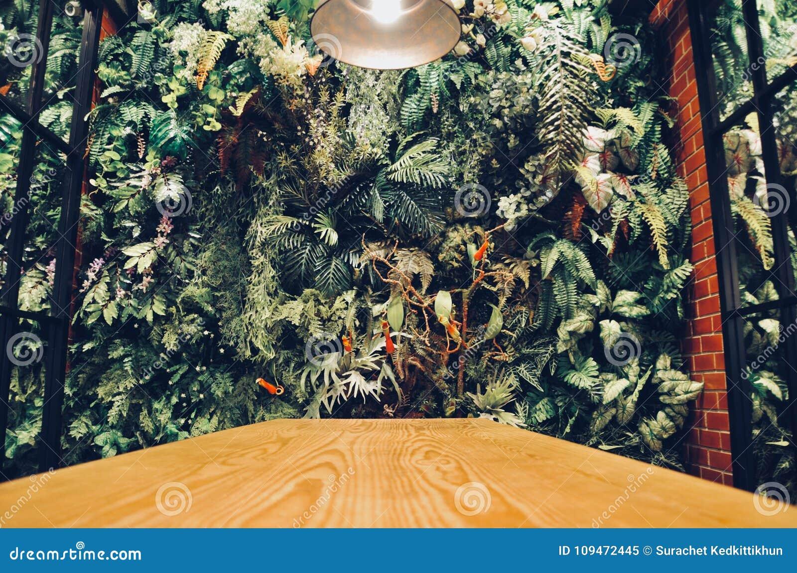 El interior moderno de la pared de un jardín llenó muchas plantas tropicales