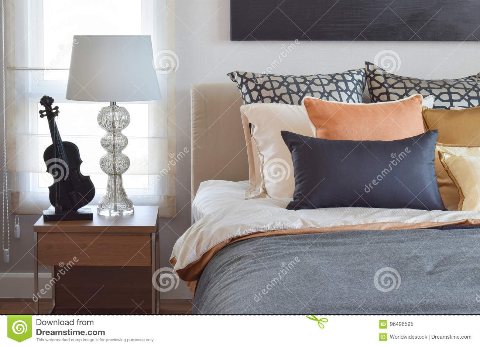 El interior moderno del dormitorio con la naranja y el oro soporta en cama y la lámpara de mesa