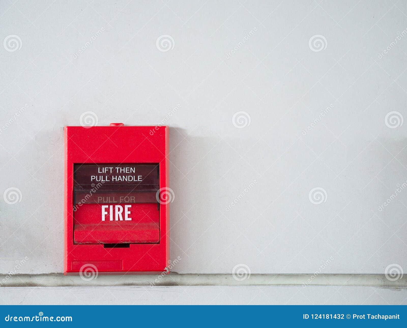 El interruptor de botón, la alarma de incendio en la pared gris para la alarma y el sistema de seguridad con el extintor viran ha