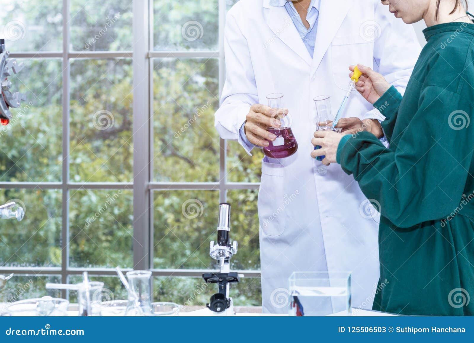El investigador hermoso mayor y la mujer hermosa joven médicos studen