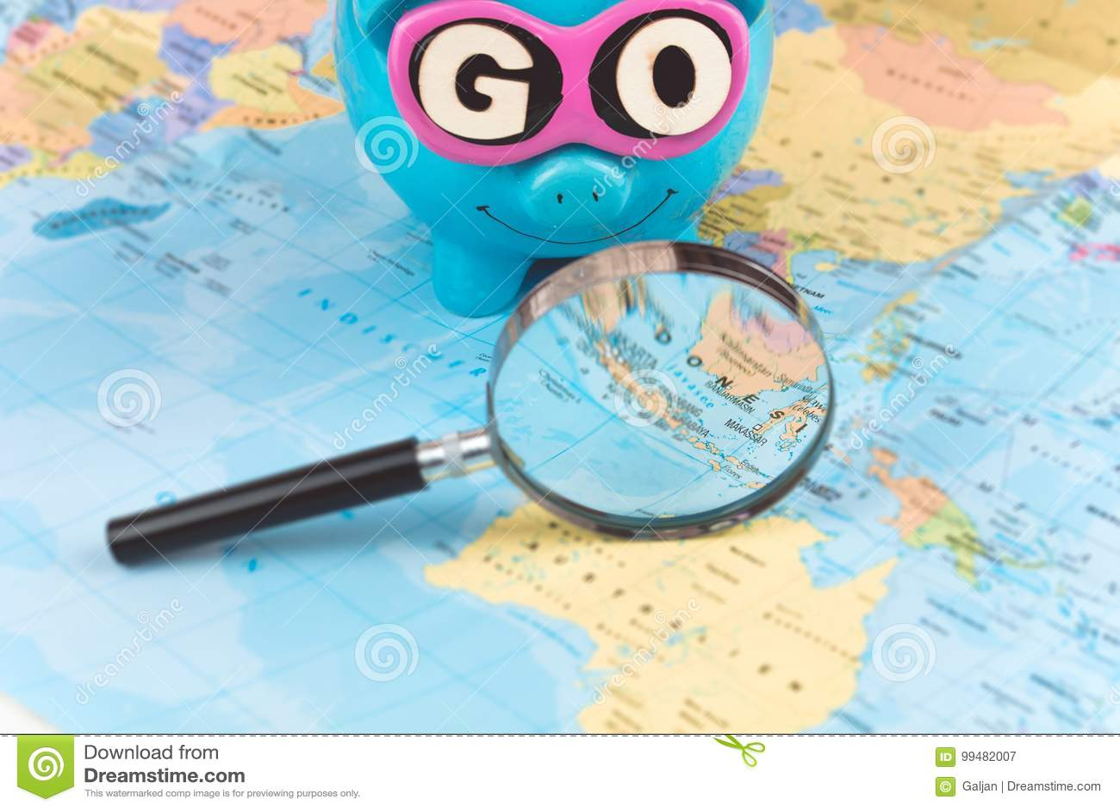 El ir a viajar Punto del enfoque de la lupa en el mapa La hucha del ahorro con las gafas de sol y VA lema que permanece en el mun