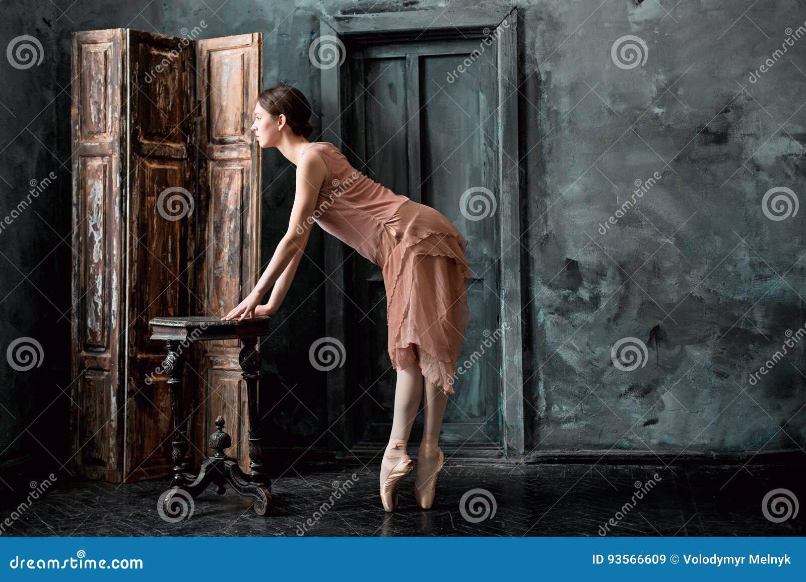 El joven y la bailarina increíblemente hermosa es de presentación y de baile en un estudio negro