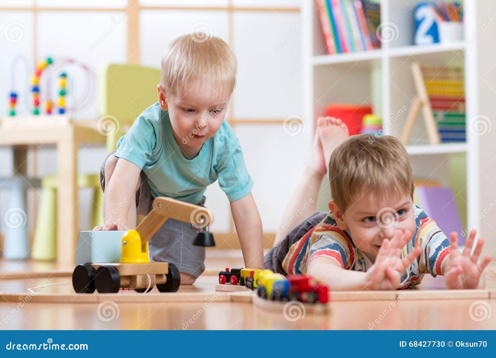 El juego de niños con el tren de madera y la estructura juegan el ferrocarril en casa, la guardería o la guardería