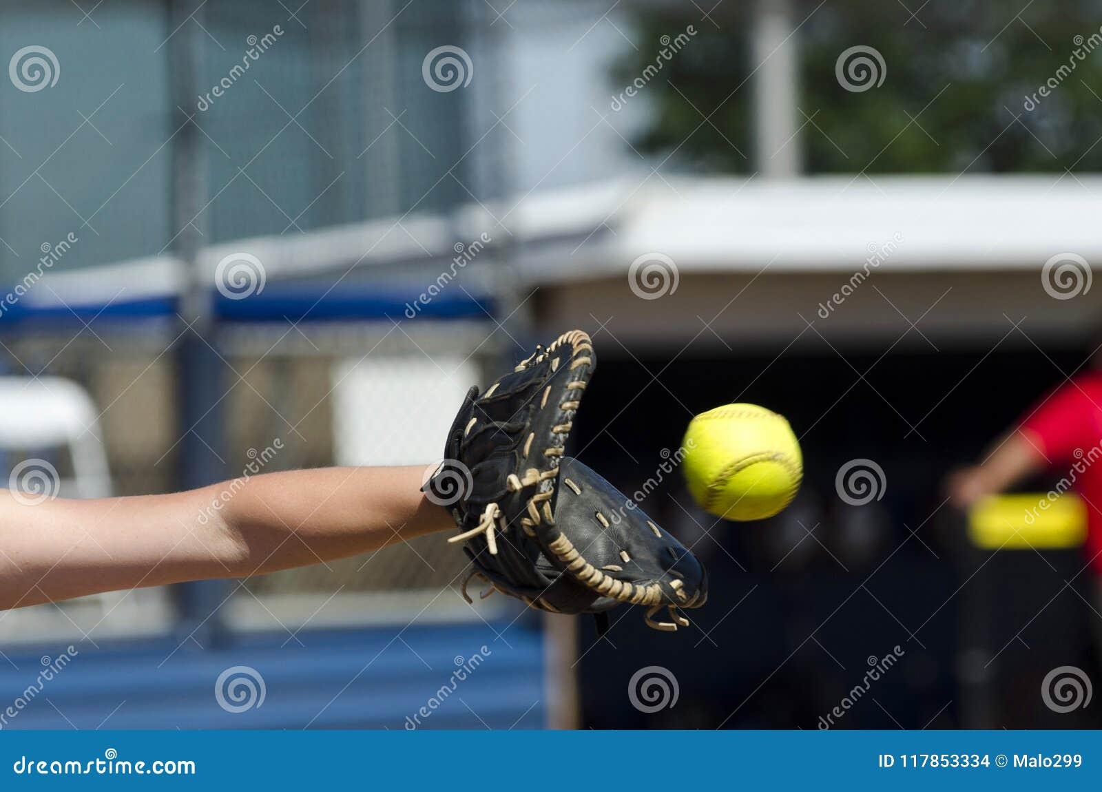 El jugador de softball alcanza hacia fuera para coger la bola