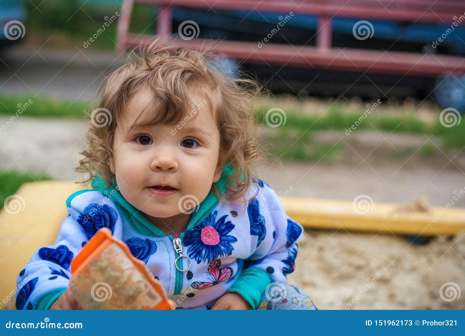 El jugar sonriente de la niña linda en la salvadera