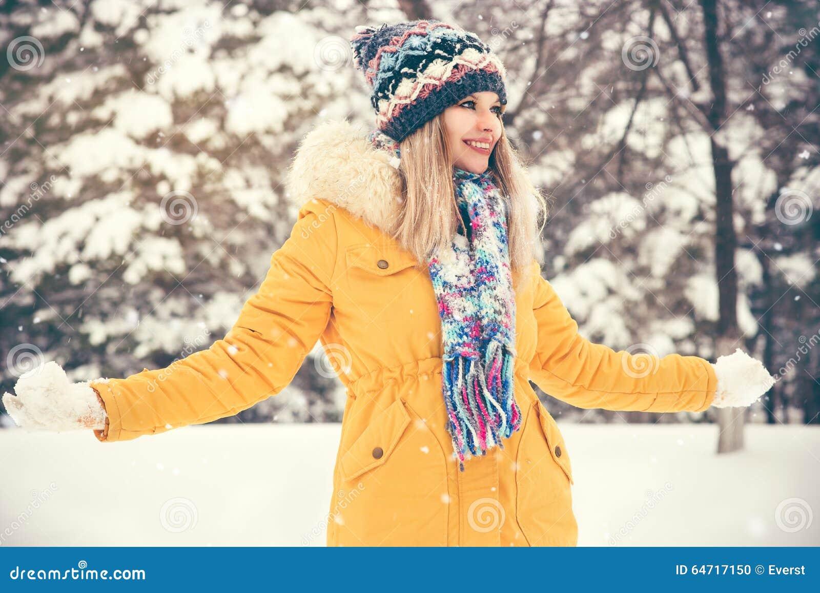 El jugar sonriente feliz del sombrero y de la bufanda de la mujer que lleva joven al aire libre