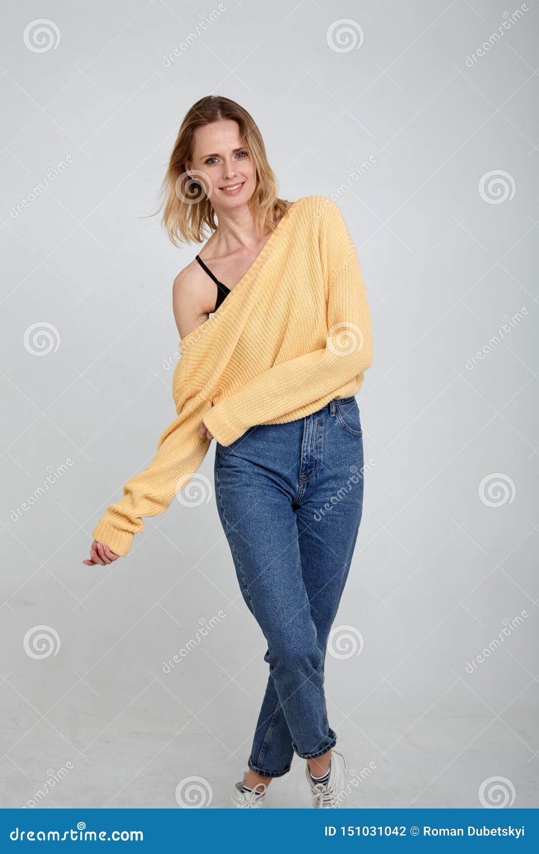 El jugar y sonrisa Un retrato en integral de un rubio hermoso, vestido en ropa elegante actitudes delante del blanco