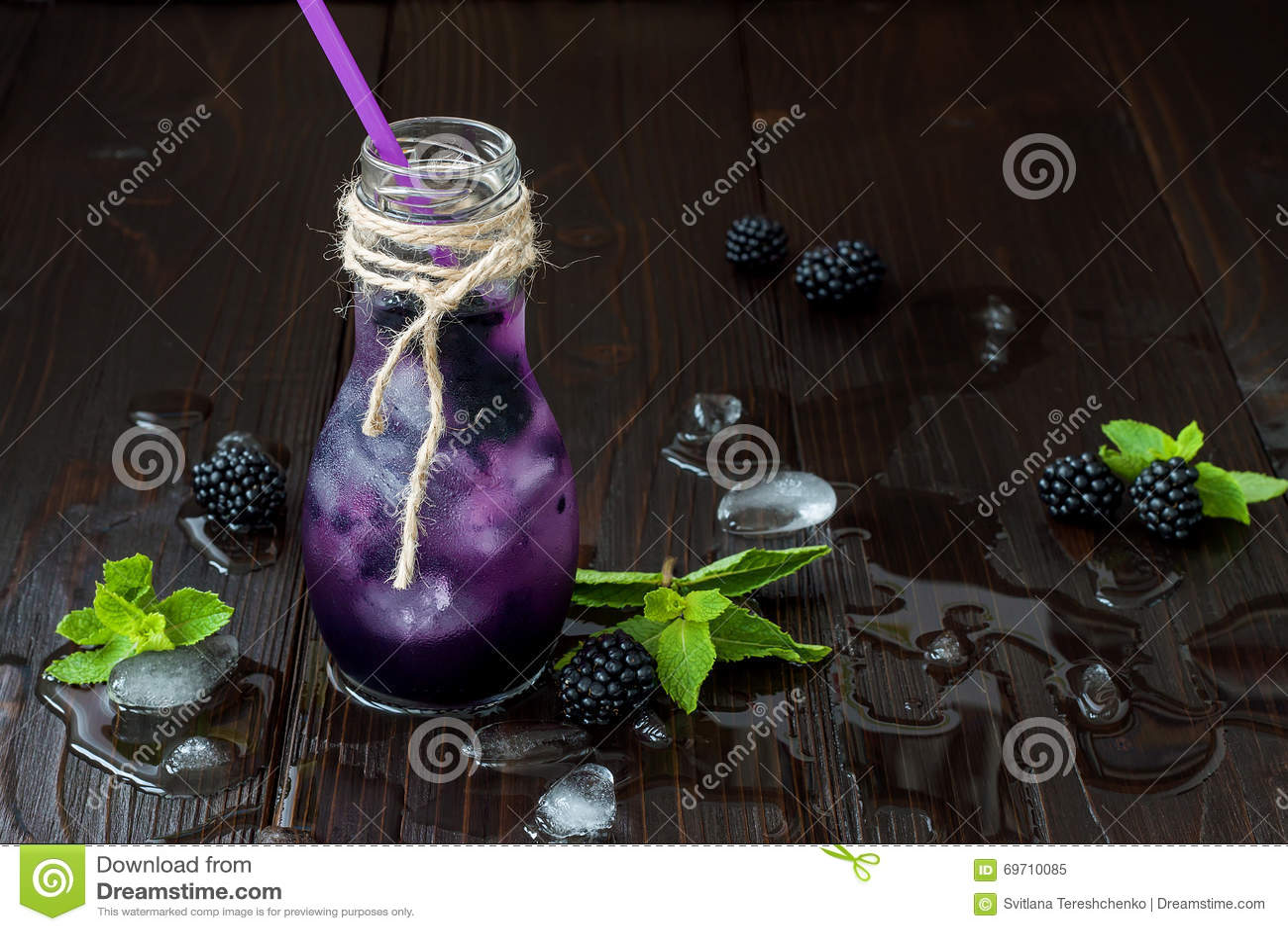 El jugo de restauración de la zarzamora en eco del vintage diseña la botella en la tabla de madera oscura rústica Bebida fría de