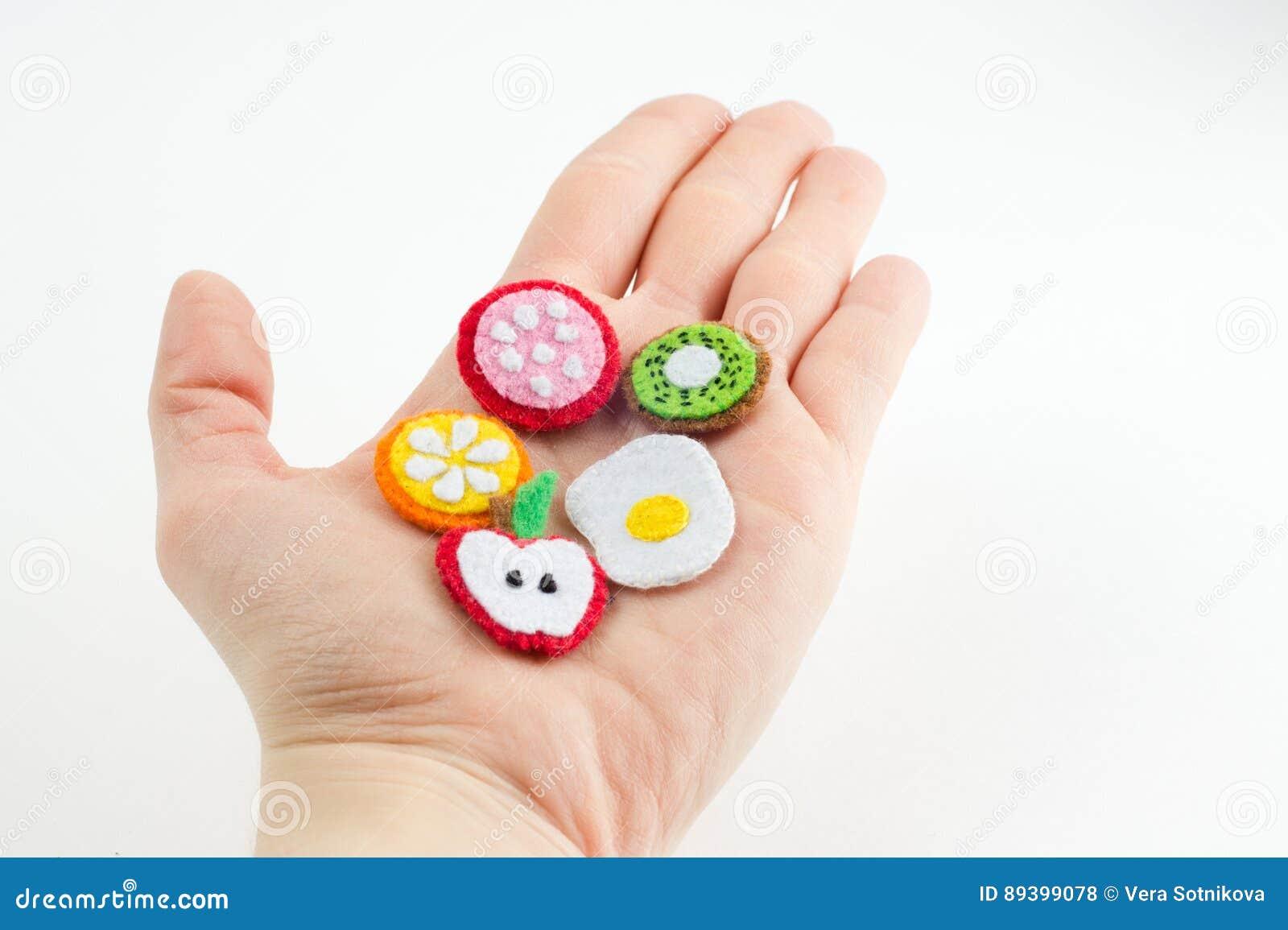 El juguete hecho a mano bajo la forma de frutas y la comida hecha del fieltro estiran