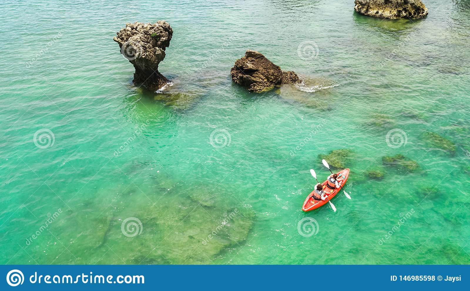 El kayaking, madre e hija de la familia bati?ndose en kajak en viaje tropical de la canoa del mar cerca de las islas, divirti?ndo