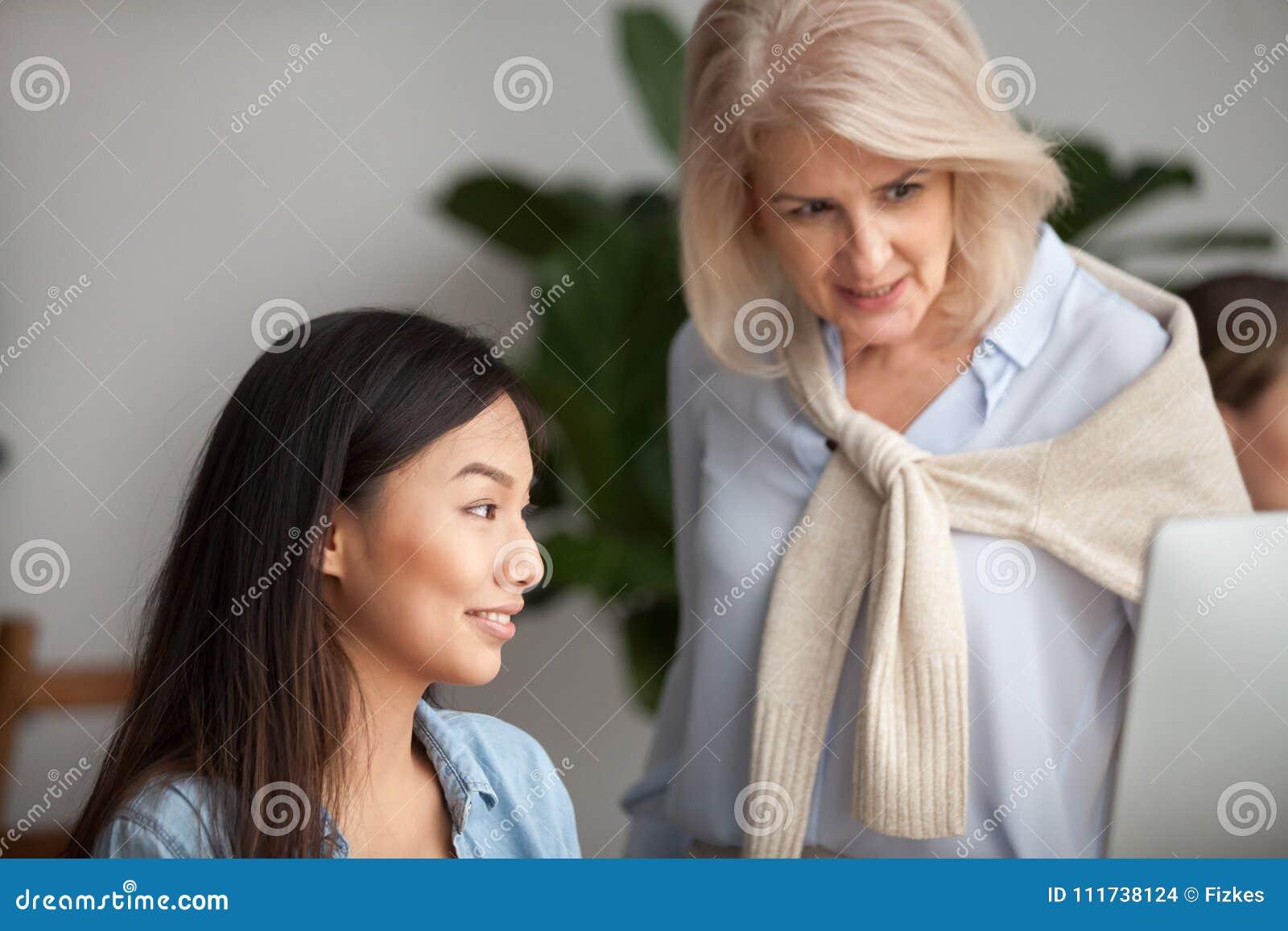 El líder envejecido sonriente que comprueba el trabajo o que enseña al asiático joven emplea