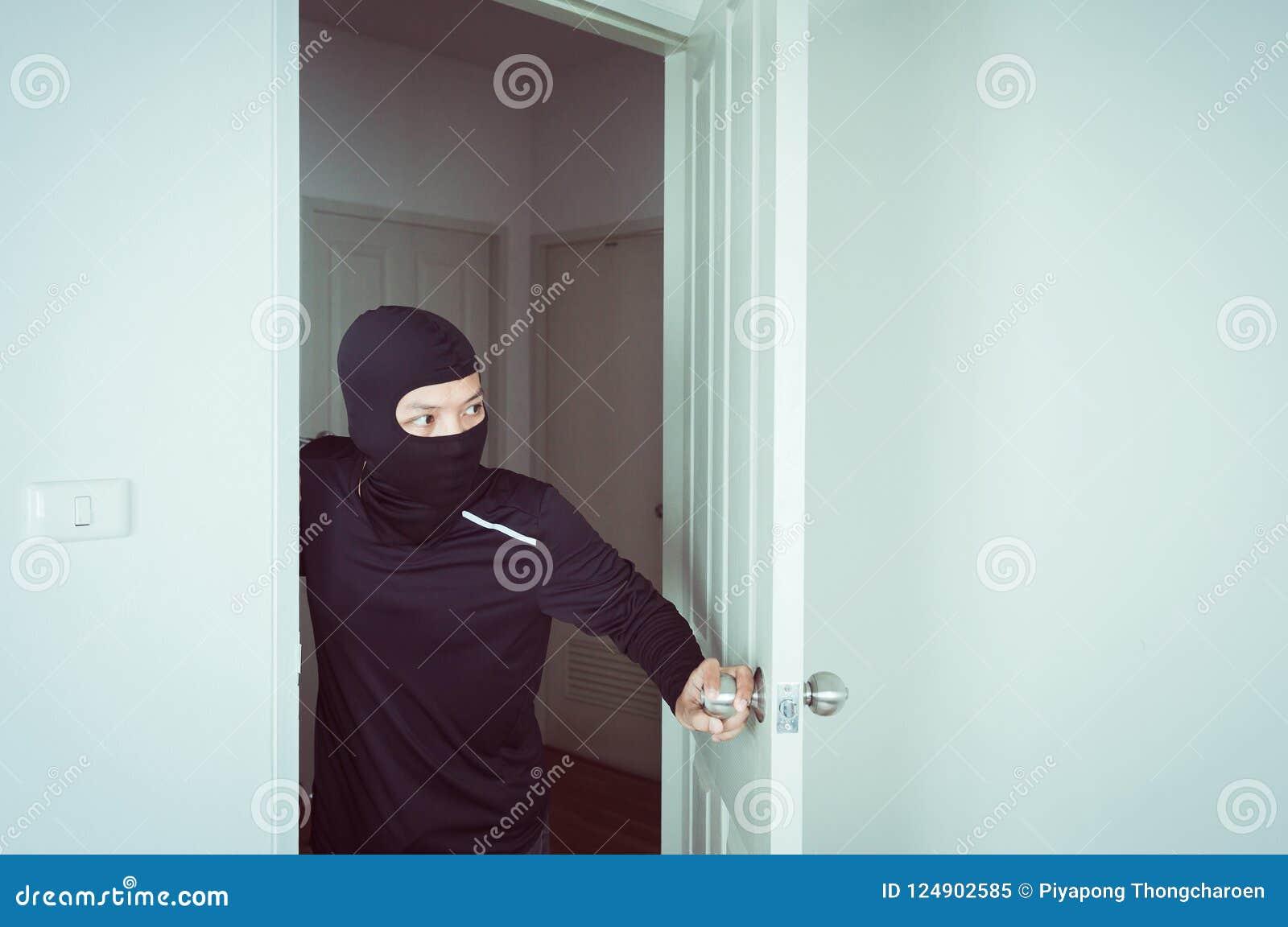 El ladrón en la máscara negra que mira y abre la puerta y el robo algo de hogar