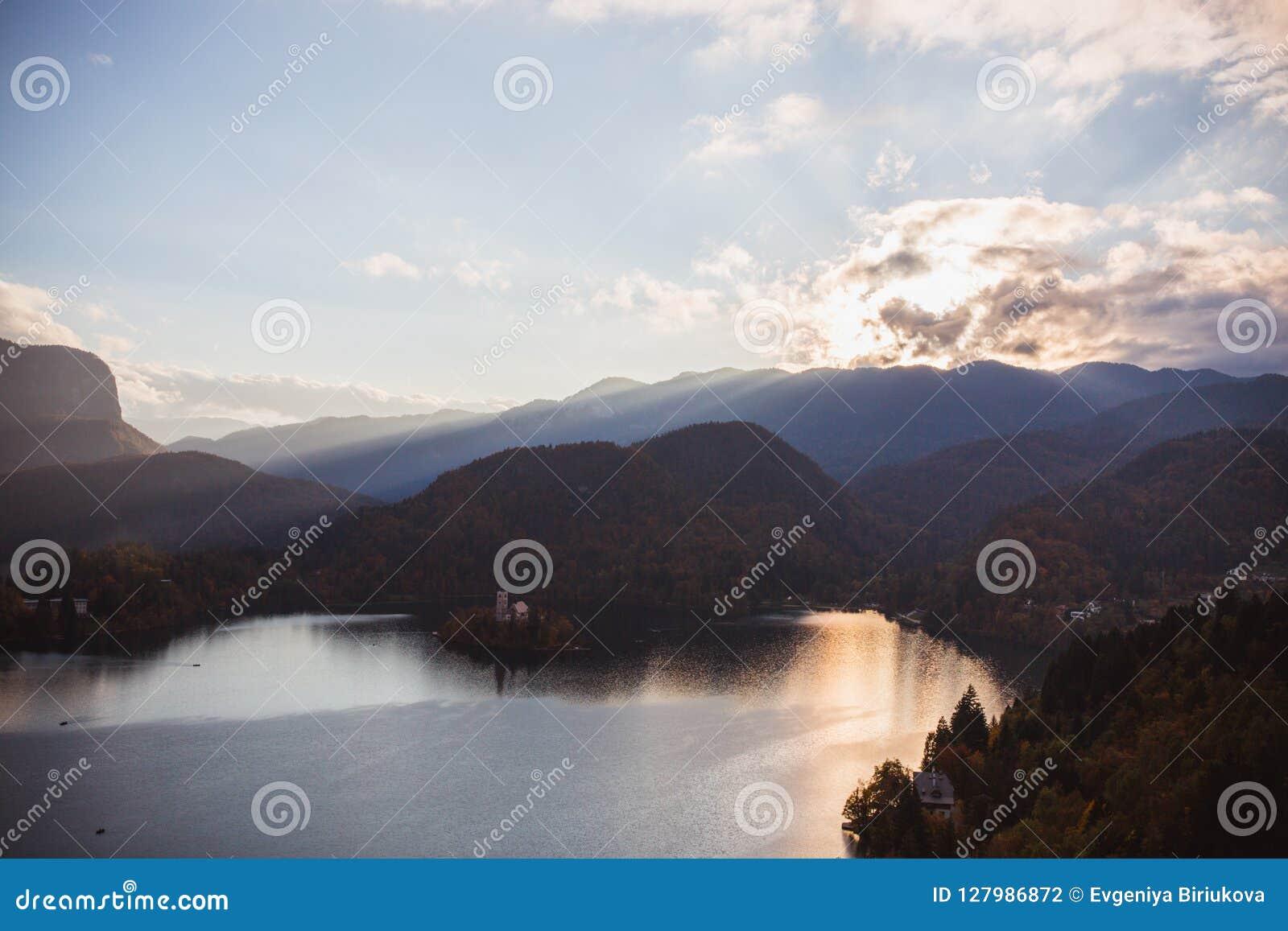El lago sangró, isla en el lago en la salida del sol en otoño o invierno