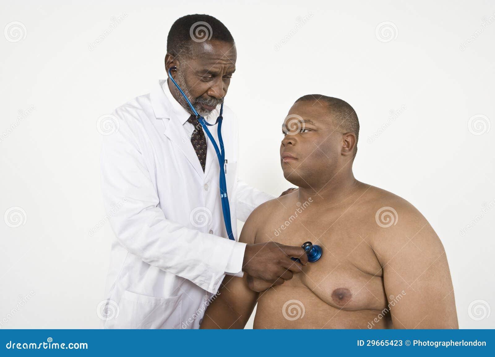 El latido del corazón del paciente del doctor Checking An Obese