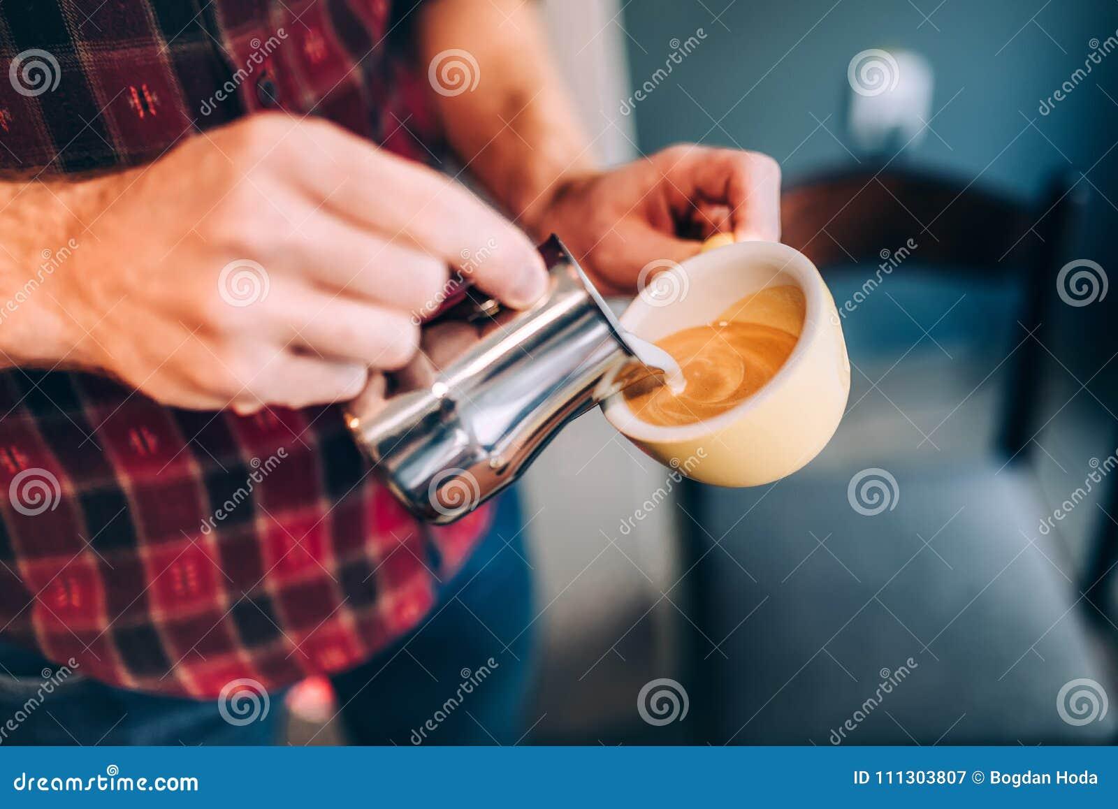 El latte de colada profesional del barista y del camarero hace espuma sobre el café, el café express y crear un capuchino perfect