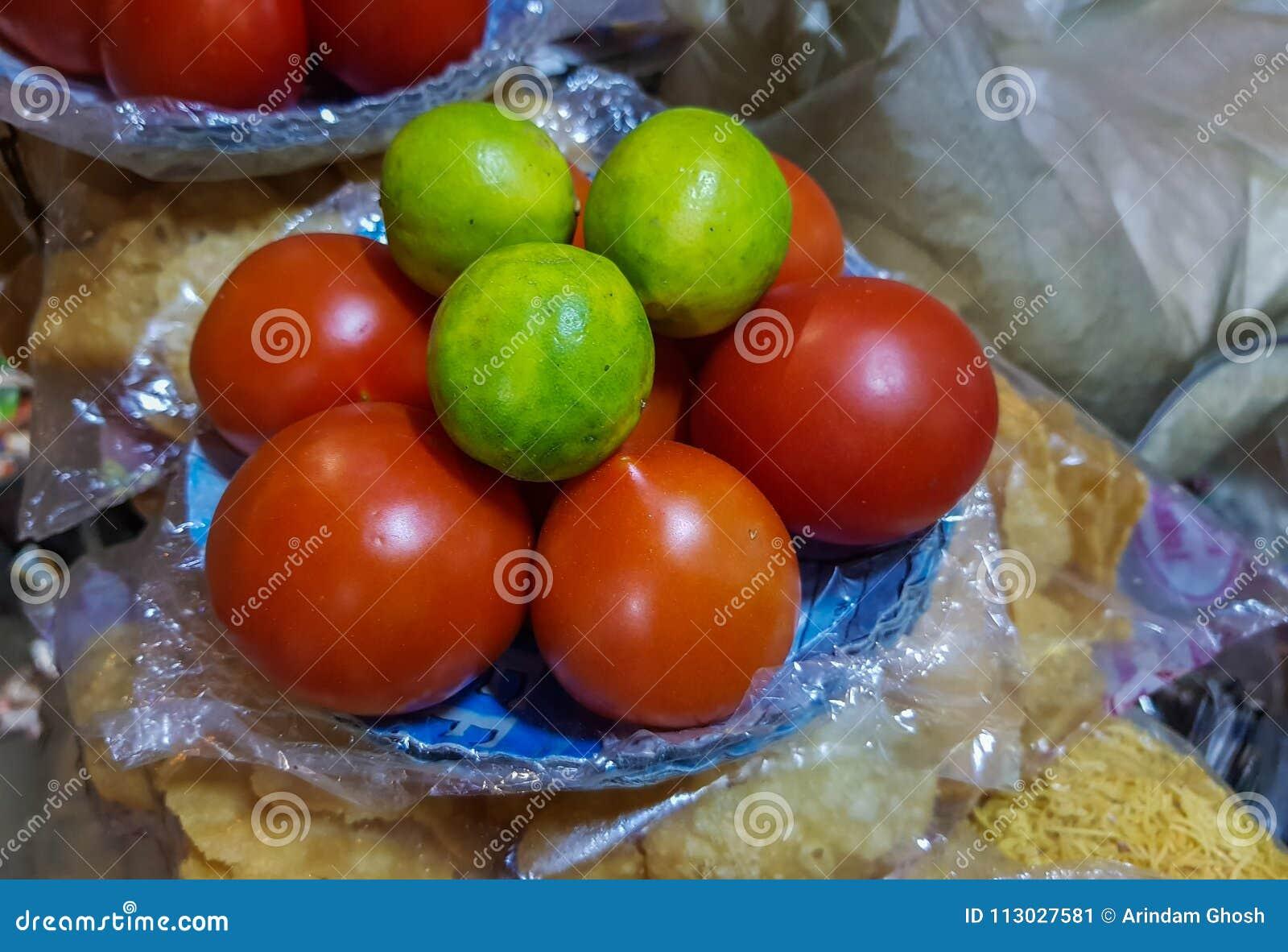 El limón y el tomate en una placa en un chaat hacen compras