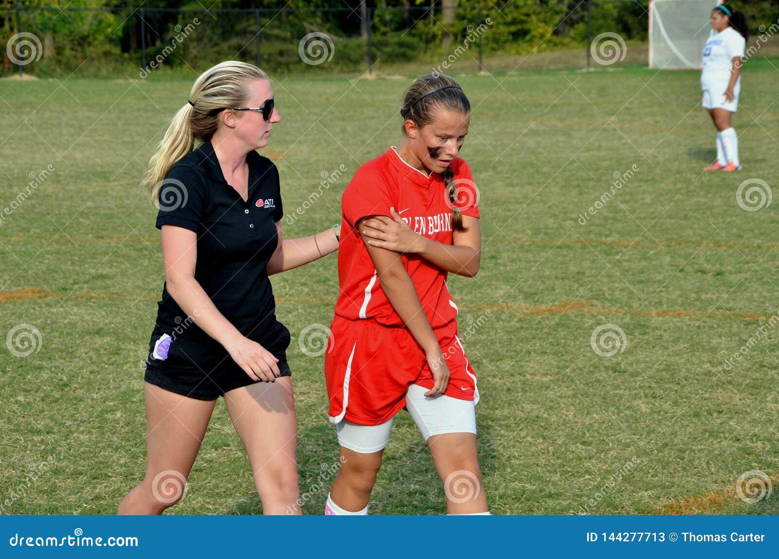 El médico ayuda a un paseo del jugador de fútbol a las líneas laterales después de conseguir herido