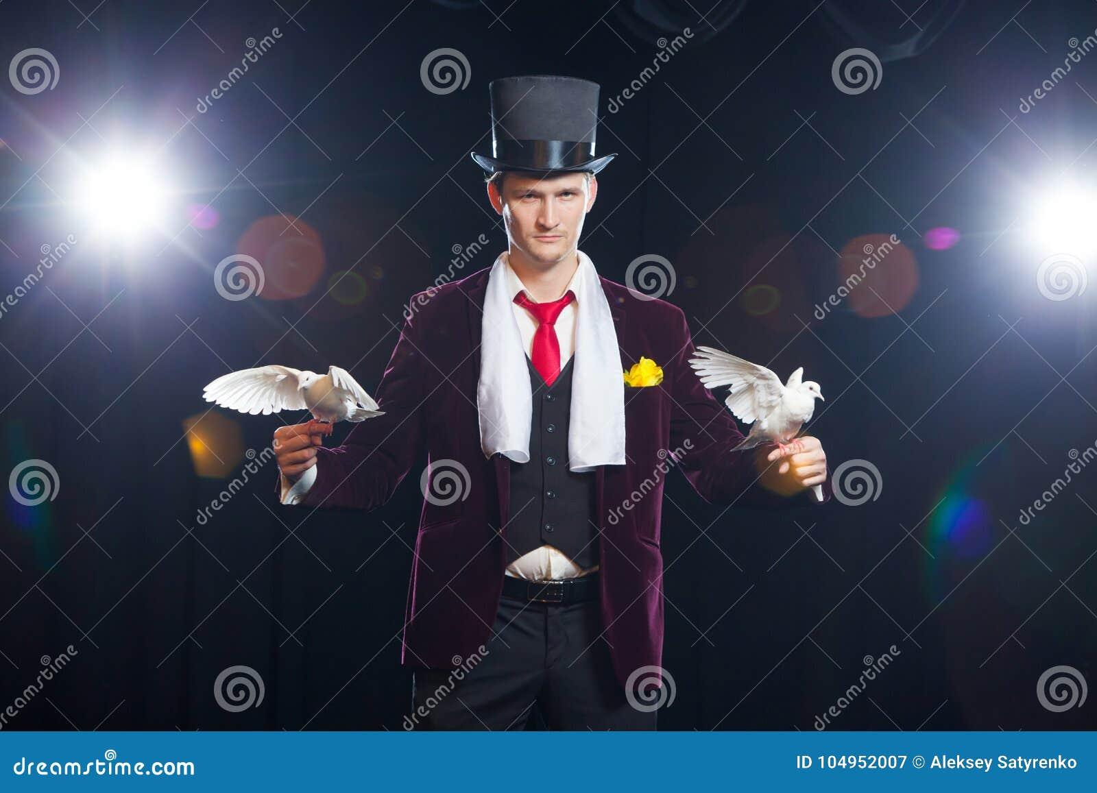 El mago con dos palomas blancas que vuelan En un fondo negro