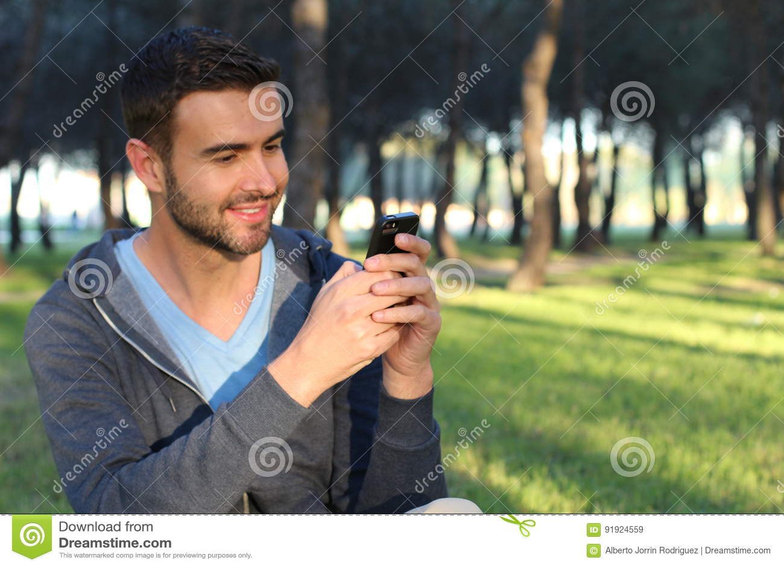 El mandar un SMS masculino alegre en el parque