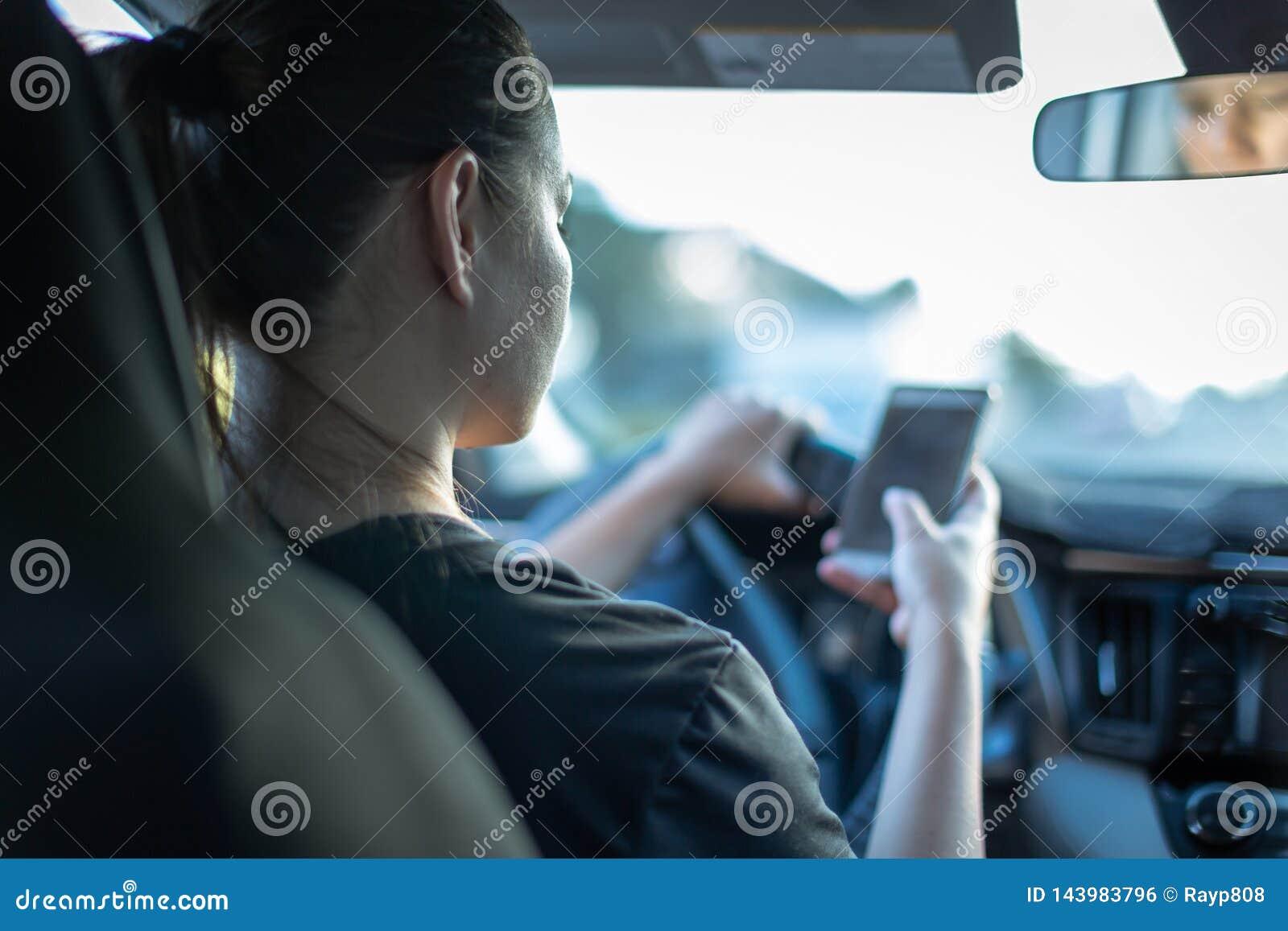 El mandar un SMS y conducción Mujer que usa el teléfono detrás de la rueda