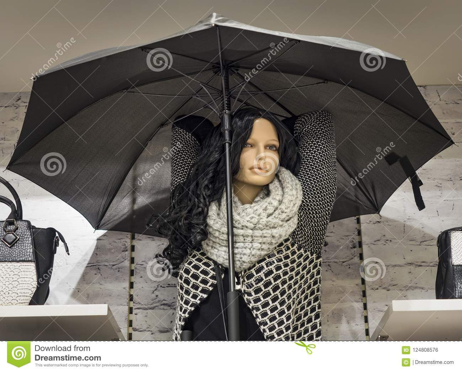 El maniquí femenino con el pelo largo se vistió en ropa del otoño en la ventana de la tienda