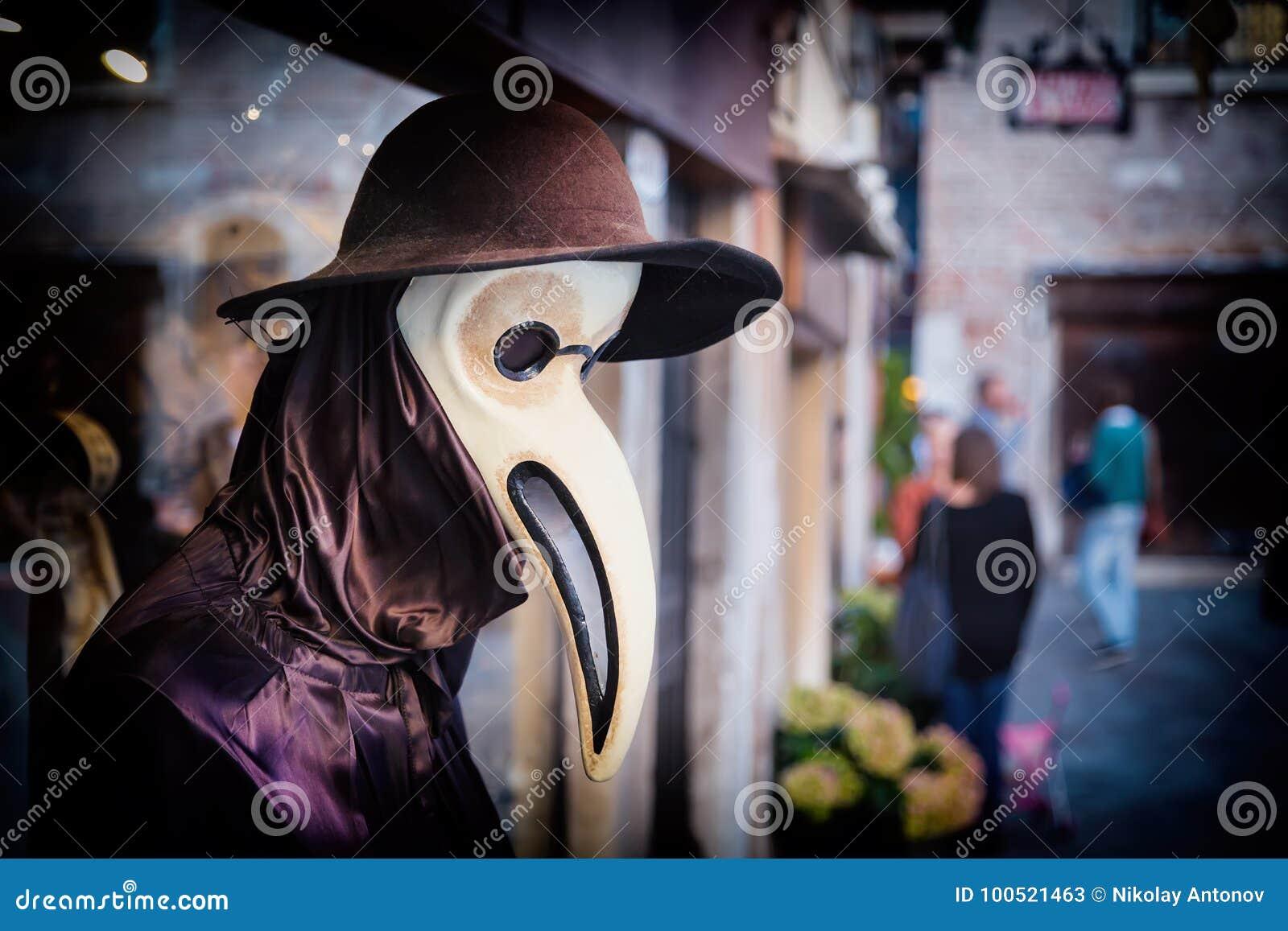 El maniquí veneciano tradicional en traje del doctor de la plaga, la máscara y el sombrero cerca hacen compras ventana en la call
