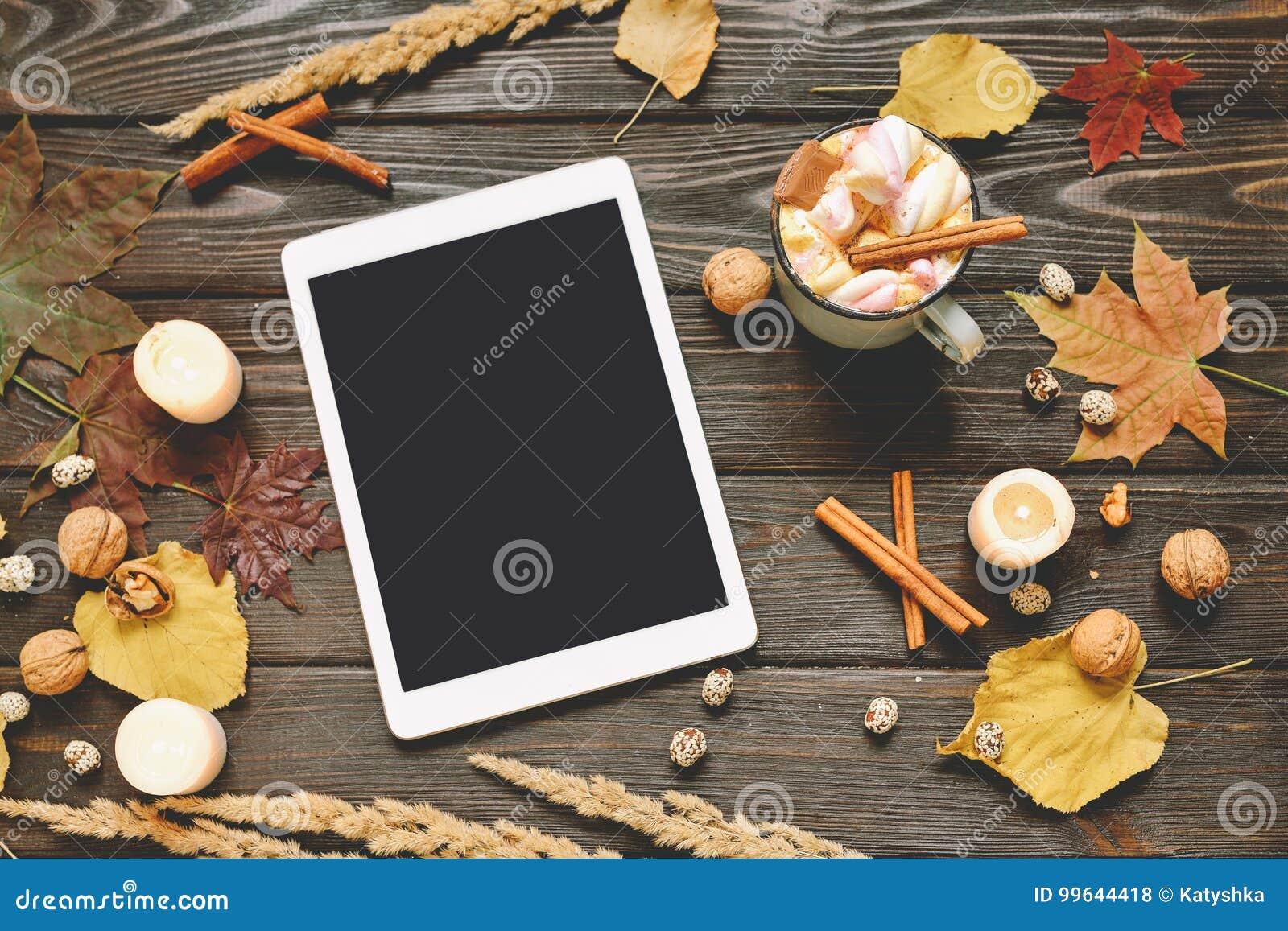 El marco del otoño hecho de caída secada se va, taza de cacao con los marshmellows, nueces, canela, tela escocesa, manzanas con m